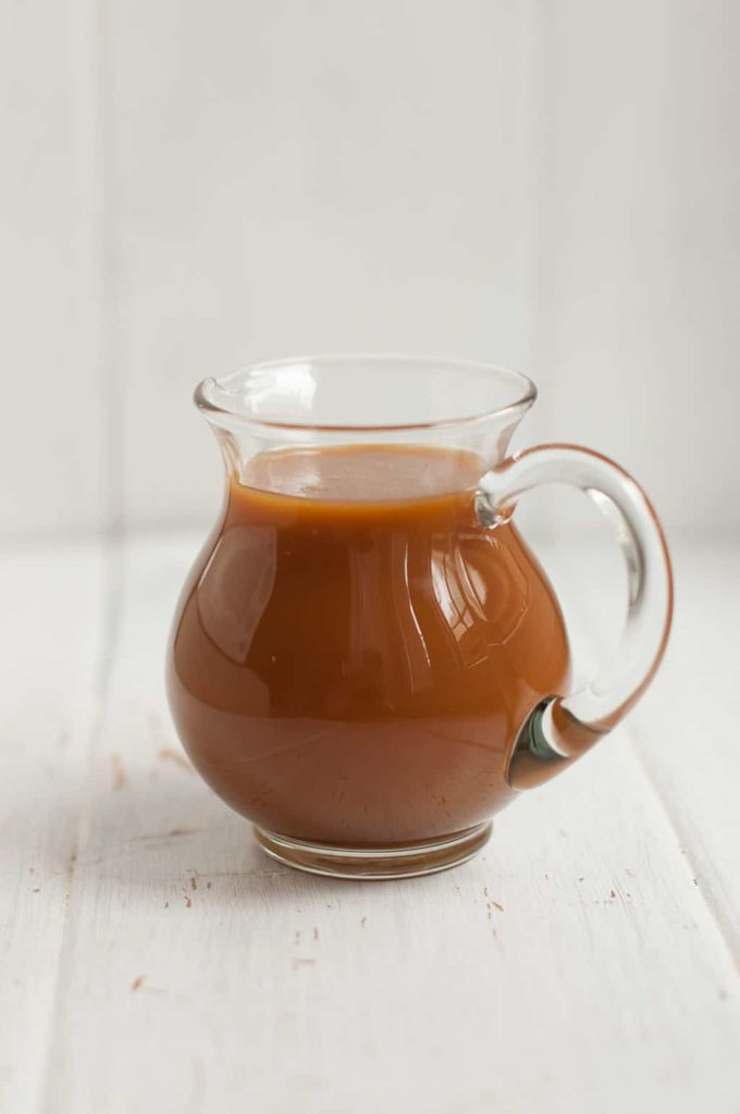 small glass jug with toffee sauce in white table