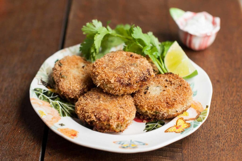spicy tuna fish cakes on a plate with coriander, wedge of lime and bowl of salt on the side