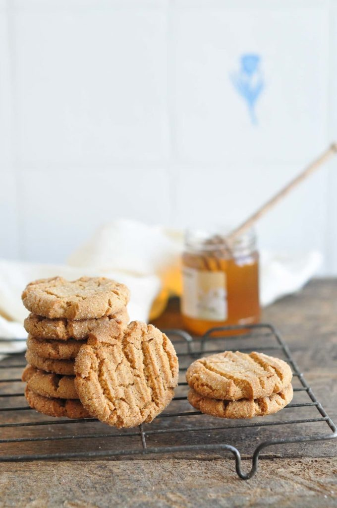 stack of ginger snap cookies on wire rack with pot of honey and white napkin