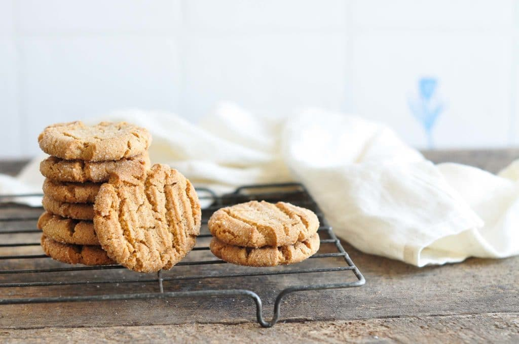stack of ginger snap cookies on cooling rack with white tea towel