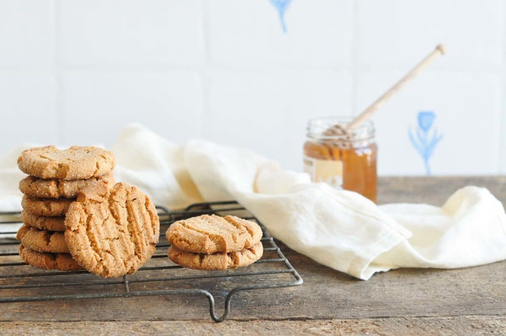 stack of ginger snap cookies on vintage wire rack with jar of honey in background
