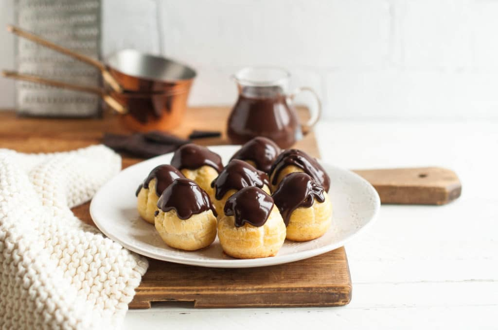 plate of profiteroles filled with creme patissiere and drizzled with chocolate ganache