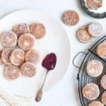 welsh cakes sprinkled in sugar on white plate and metal wire rack