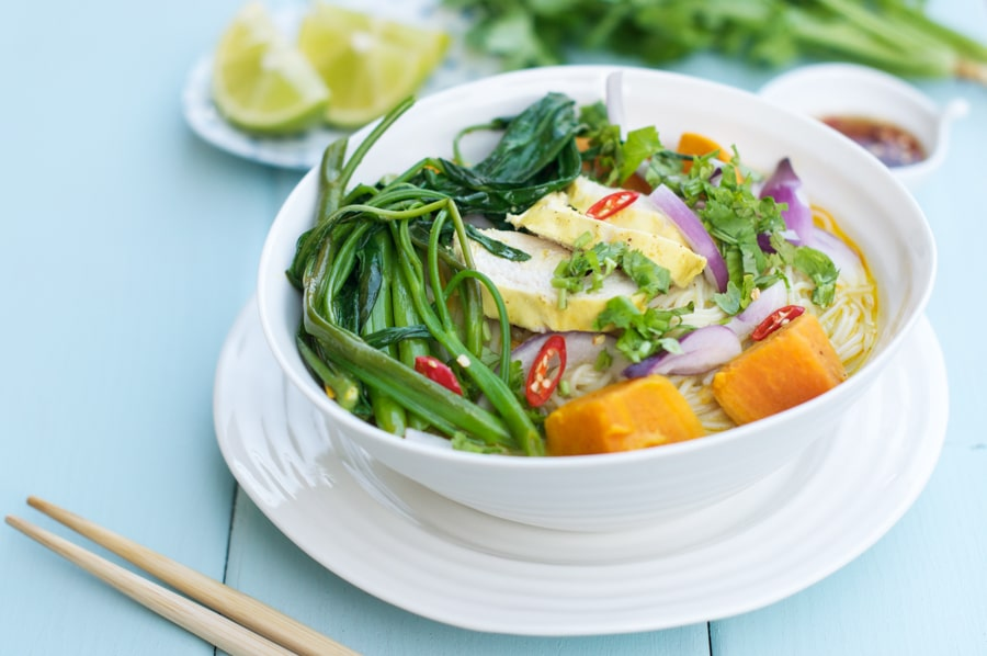 vietnamese chicken curry soup in white bowl on blue table