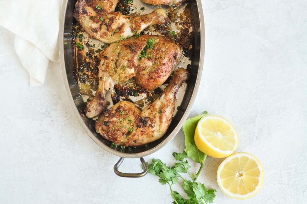 grilled thai chicken in pan with cut lemons and cilantro