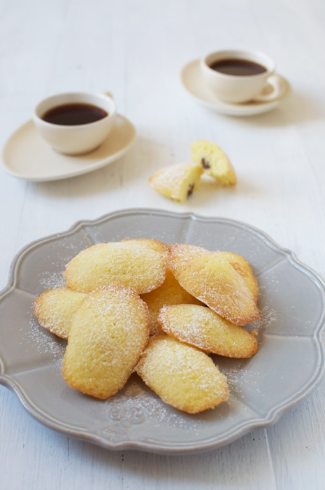 plate of madeleines with nutella with cups of coffee in background