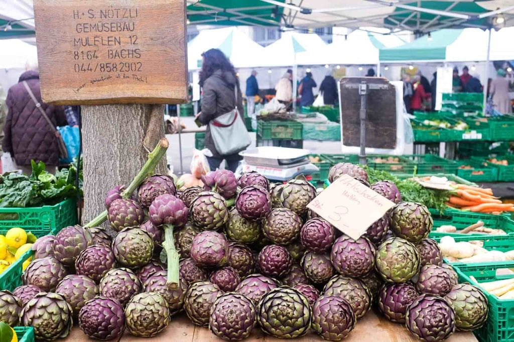 stack of fresh globe artichokes at the farmers markets in zurich