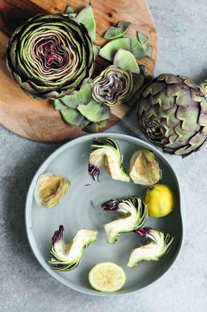 sliced globe artichoke with artichoke hearts in bowl of water with lemon