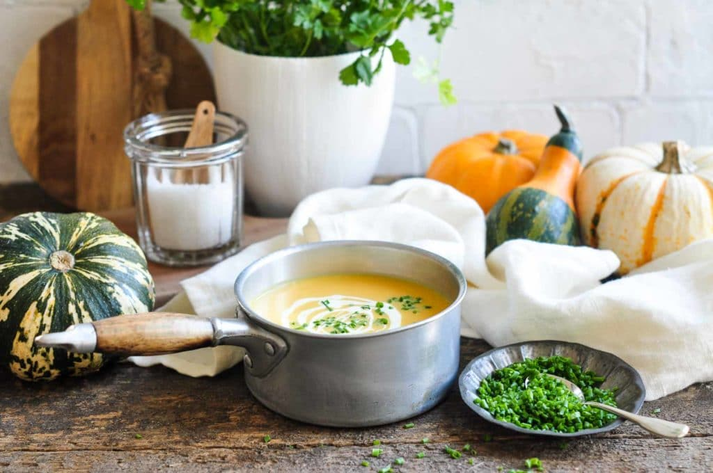 roast pumpkin soup in saucepan with small plate of chopped herbs and fresh squash