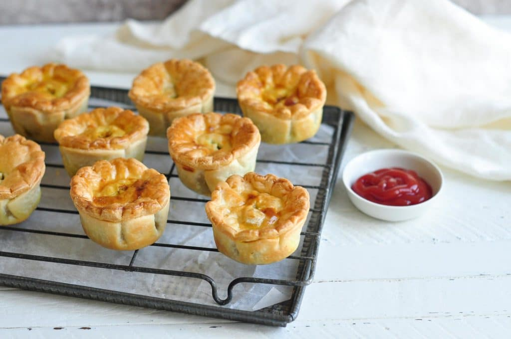 aussie meat pies on wire rack with white tea towel