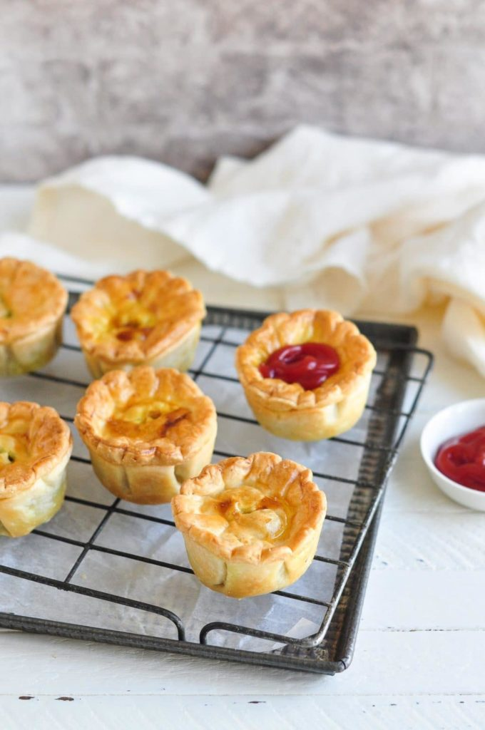 aussie meat pies on wire rack on baking tray with ketchup