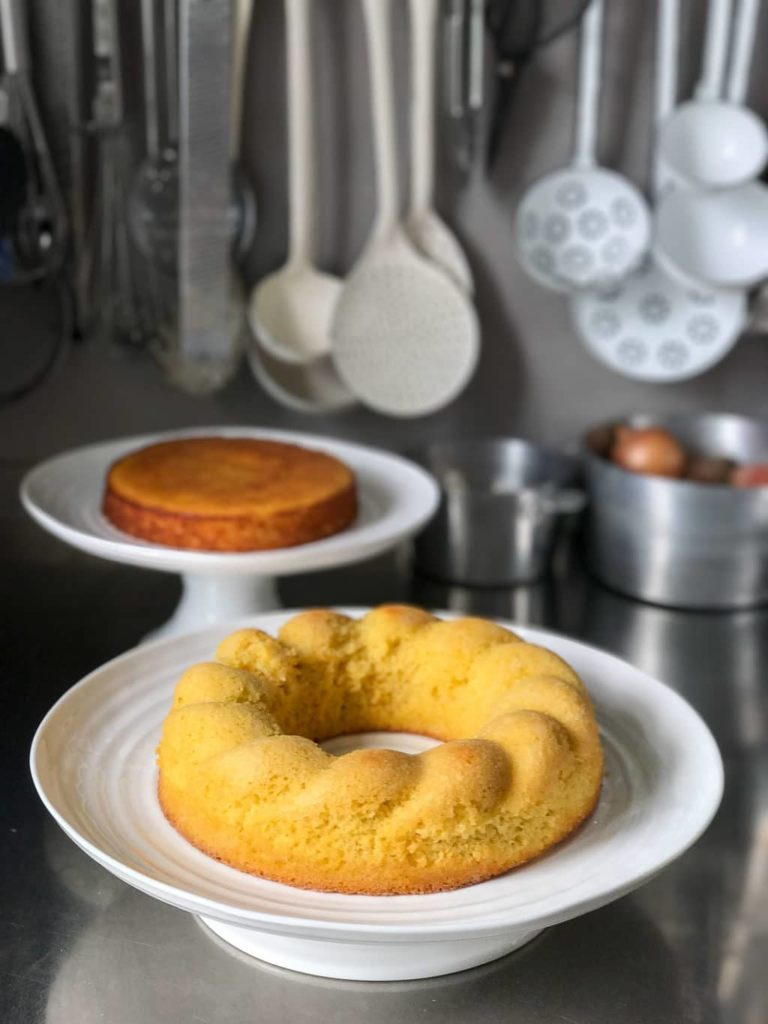 gluten-free lemon cake on white cake stand on stainless steel bench