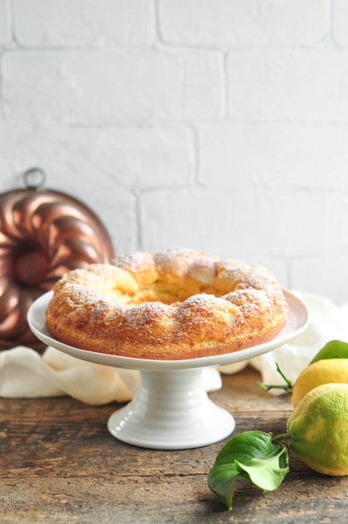 gluten-free lemon cake on cake stand with fresh lemons on wooden table