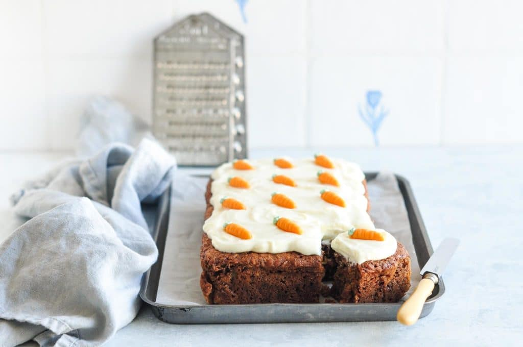 carrot cake on baking tray with vintage graters in background