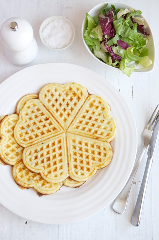 two savoury waffles on white plate with cutlery, salt and pepper