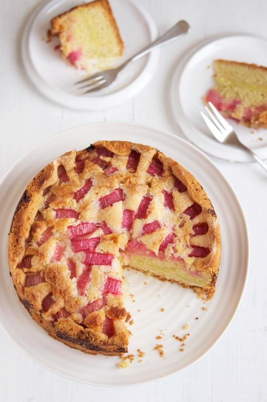 rhubarb custard tea cake on white cake stand