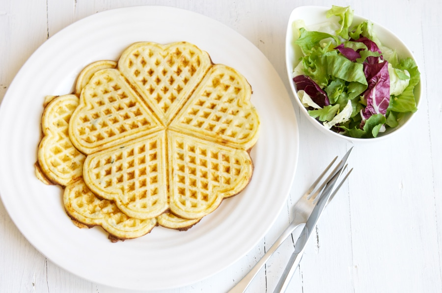 savoury waffles on white plate with bowl of salad