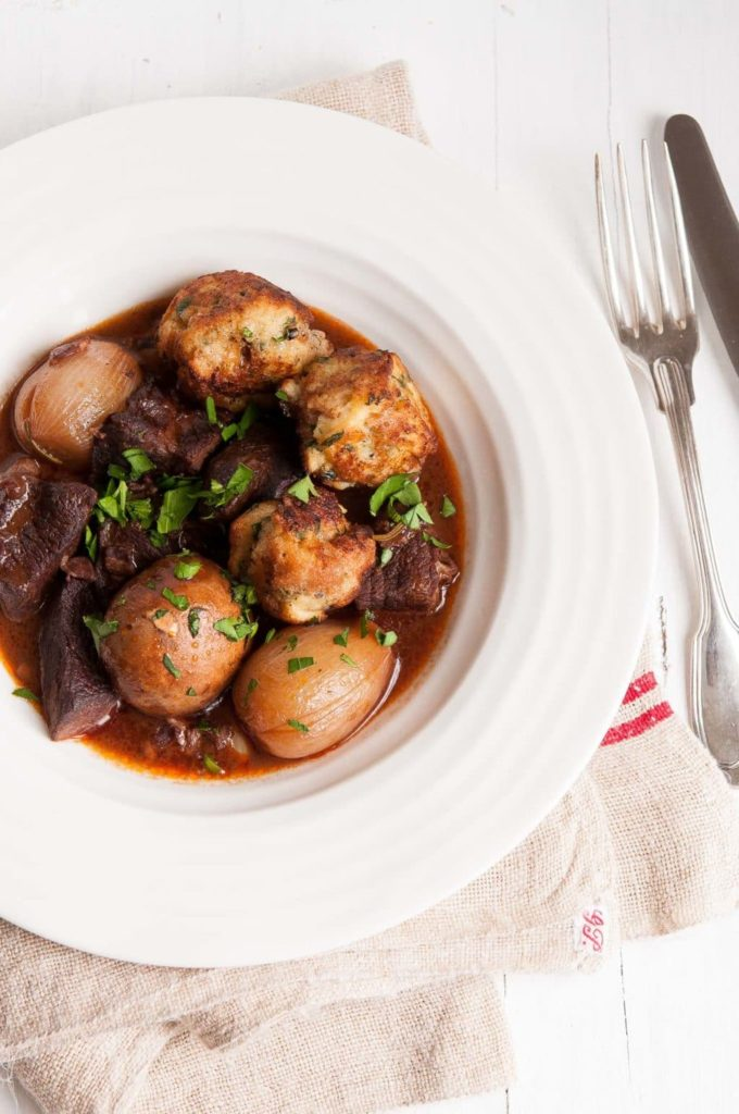 beef bourguignon with baguette dumplings on white plate with vintage cutlery