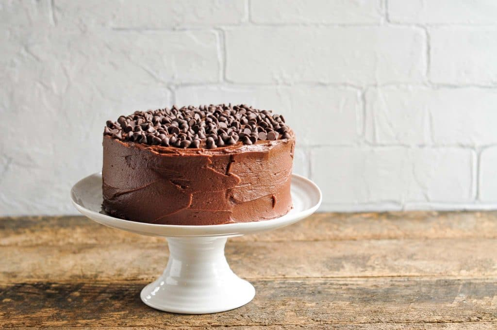 ultimate chocolate cake on large white cake stand