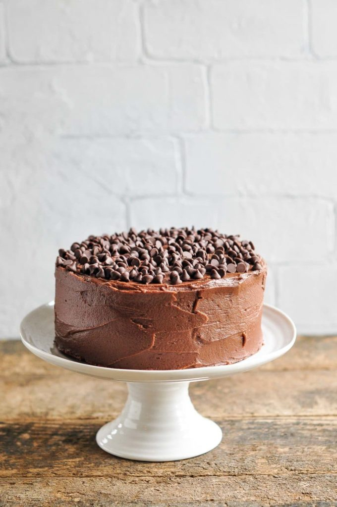 ultimate chocolate cake on white cake stand on wooden table