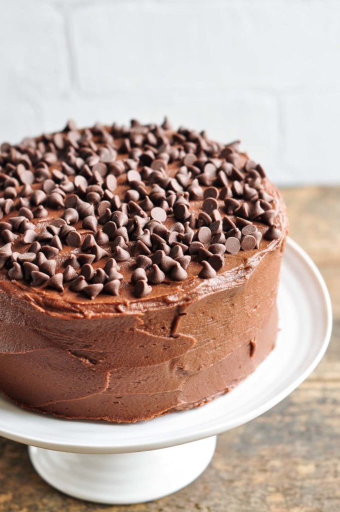 ultimate chocolate cake on white cake stand with lots of chocolate chips on top