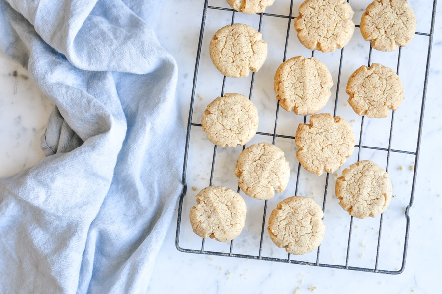 tahini cookies on wire rack with blue tea towel