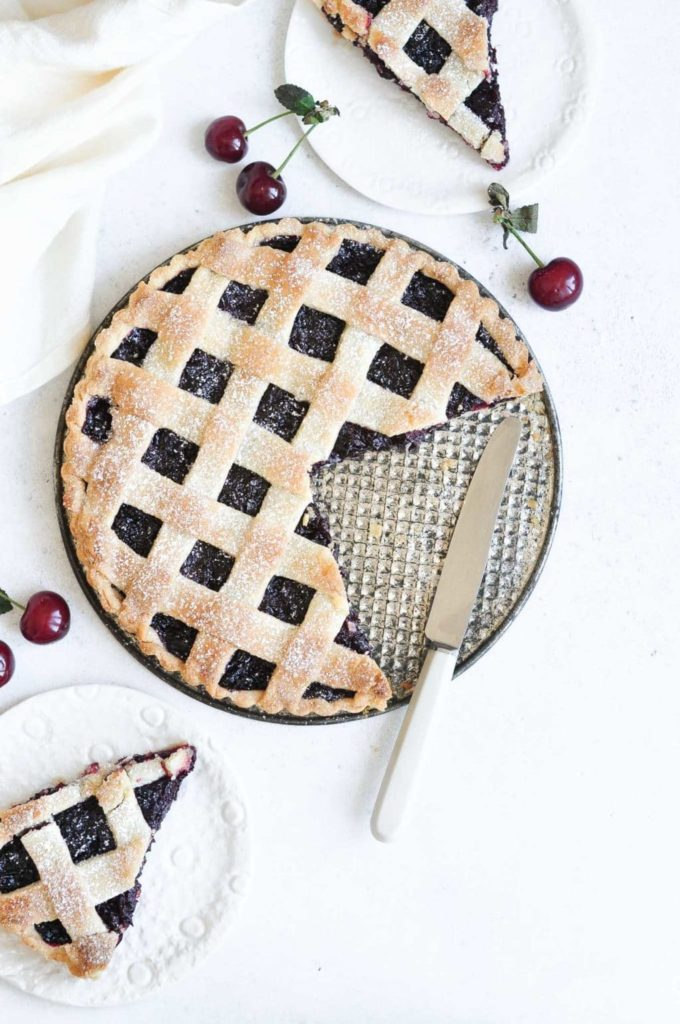 two slices of cherry pie with lattice pie crust on white plates