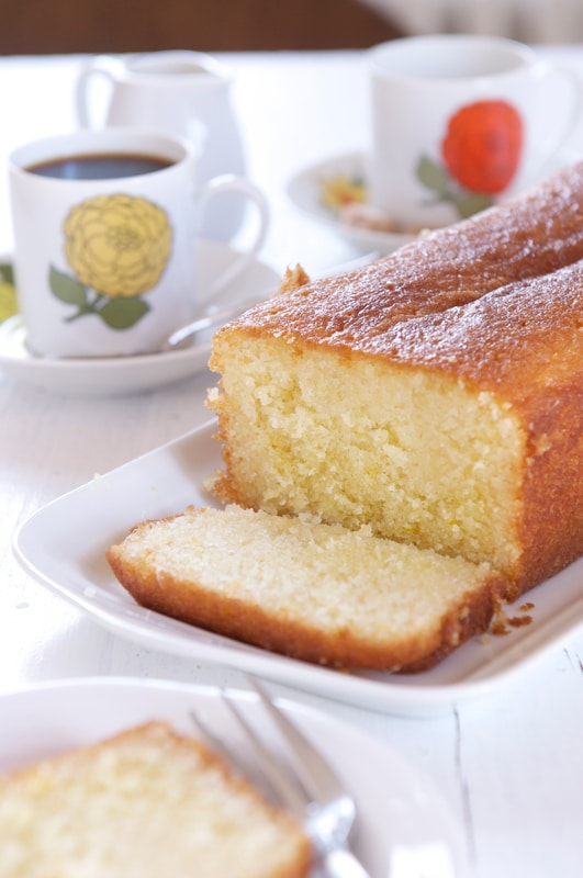 lemon syrup cake sliced with coffee cup