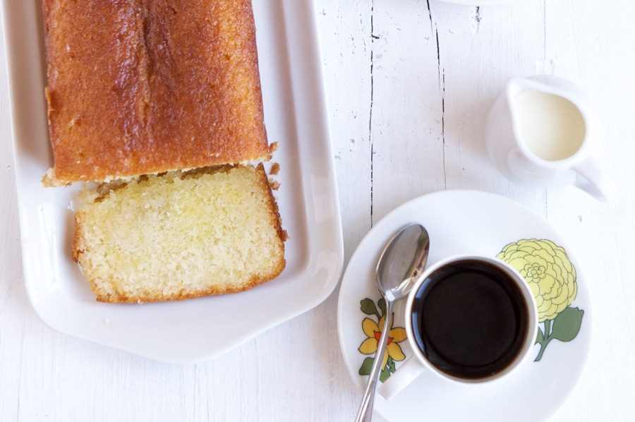 lemon syrup cake on plate with cup of coffee