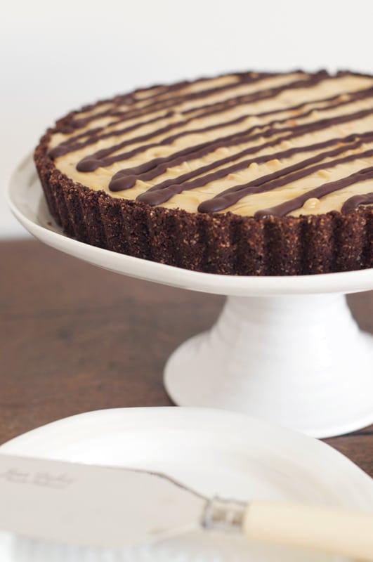 chocolate peanut butter cheesecake on white cake platter