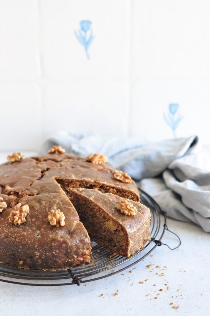easy apple cake with caramel glaze on wire rack with blue teatowel