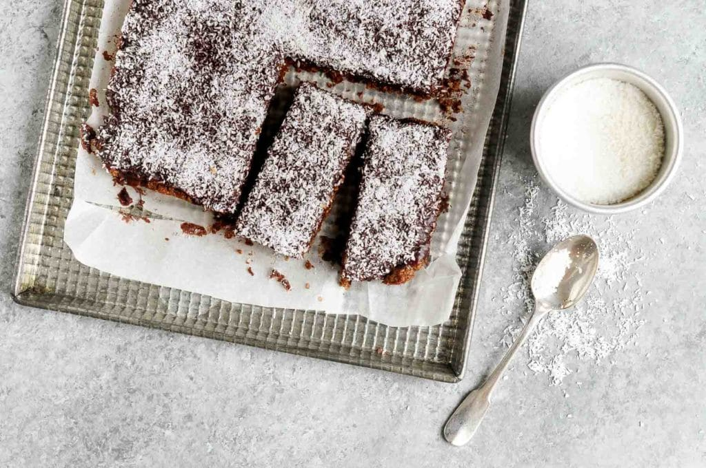 slices of chocolate coconut bars on metal tray with sprinkled coconut