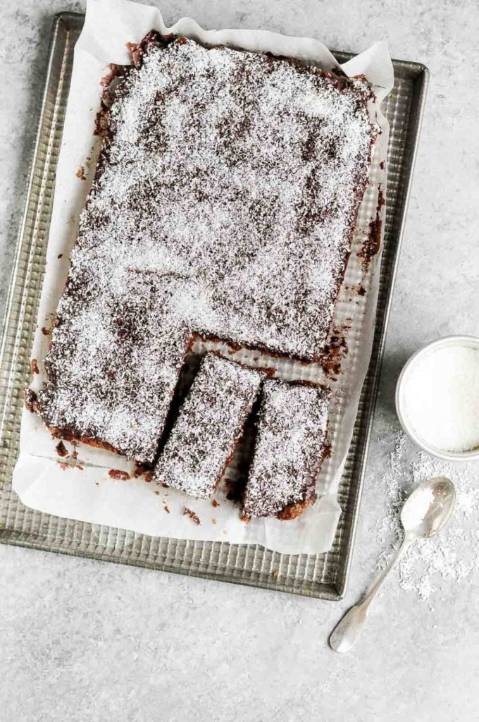 slices of chocolate coconut bars on metal tray with baking paper