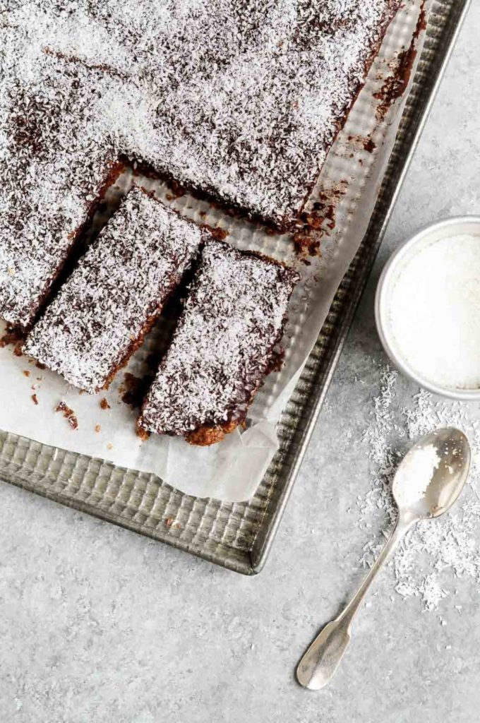two slices of chocolate coconut bars on metal tray with sprinkled coconut