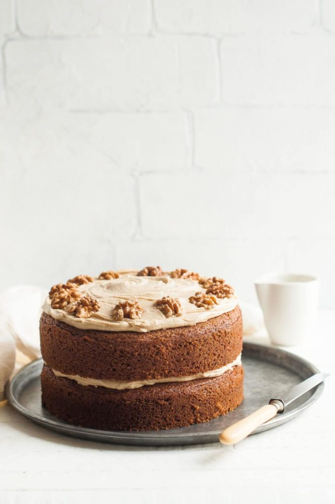 coffee and walnut cake on tray with knife and milk creamer in background