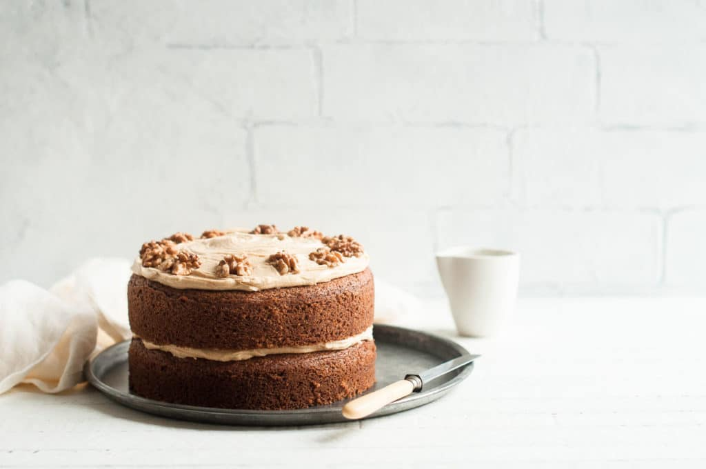 coffee and walnut cake on metal tray with cake knife