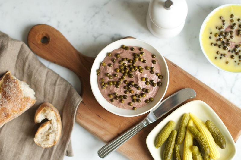 chicken liver pate with green peppercorns on wooden board