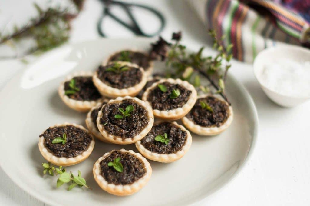 mushroom tarts on beige plate with micro herbs
