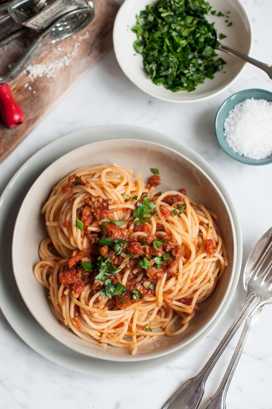 bowl of spaghetti bolognese with bowl of herbs and sea salt