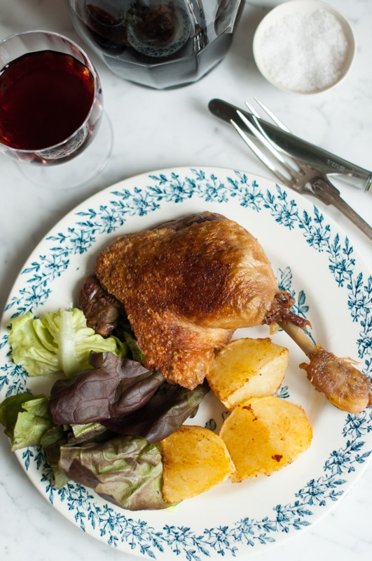 crispy and golden duck confit with roast potatoes and salad on white plate with blue pattern