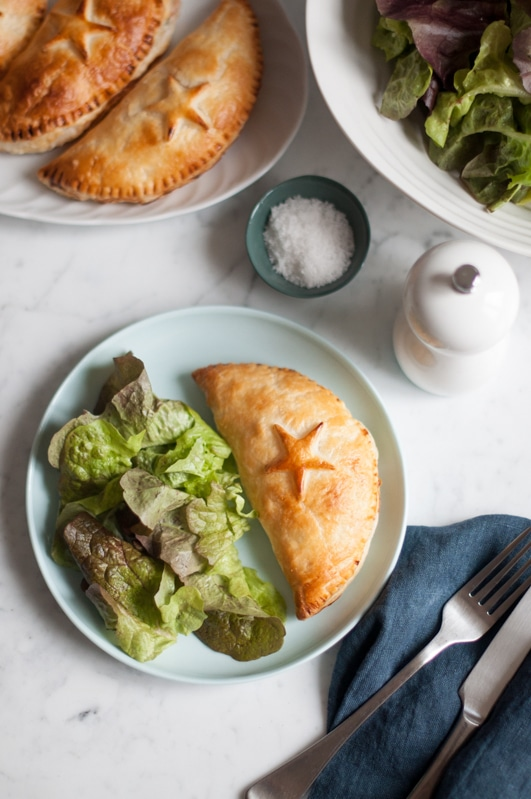 ham and cheese hand pies on blue plate with salt and pepper