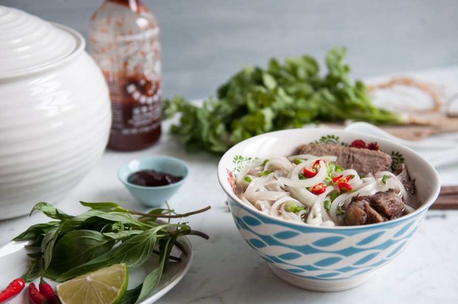bowl of beef pho noodles soup with herbs on wooden board in background