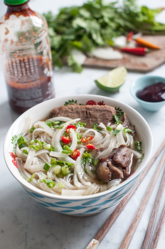 bowl of beef pho noodle soup with bottle of sriracha sauce