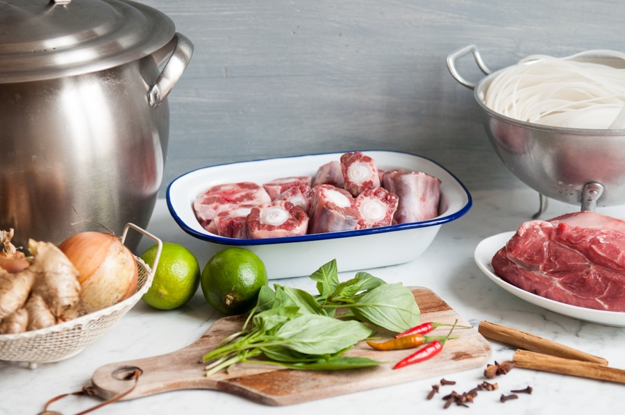 plate of raw oxtail and ingredients for making vietnamese beef pho