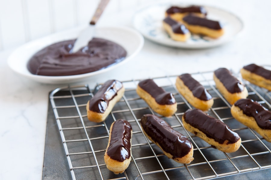 chocolate eclairs with plate of chocolate ganache in background