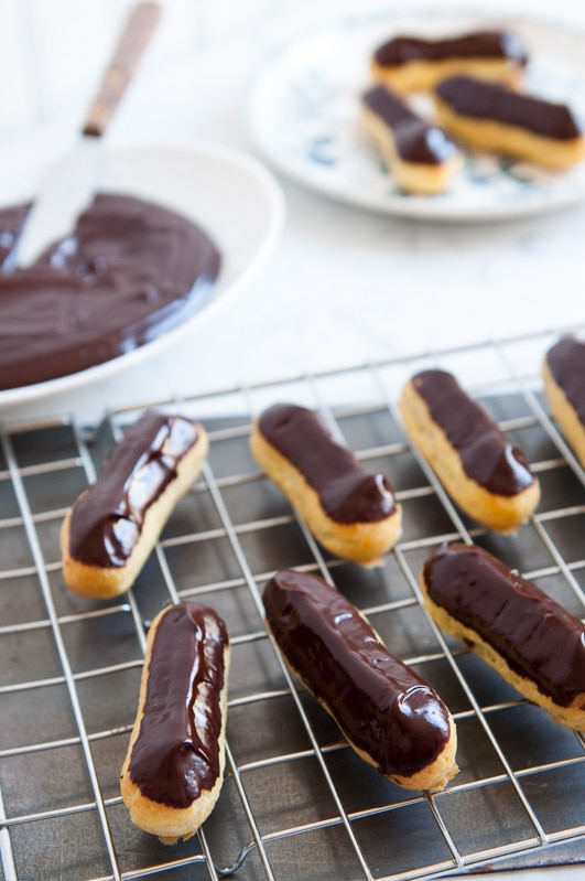 chocolate eclairs on wire rack
