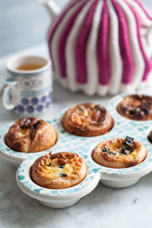 custard tarts with teapot in background with tea cosy