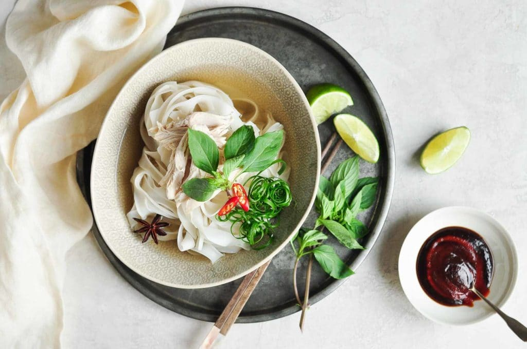 chicken pho recipe with vietnamese chicken pho in bowl on metal tray with fresh herbs and lime wedges