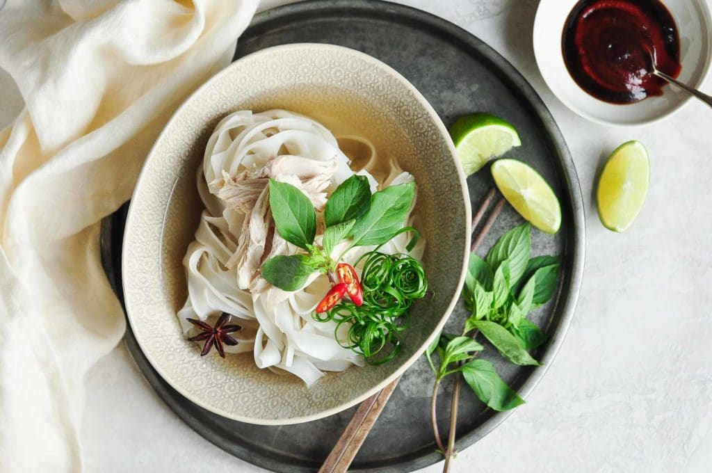 bowl of instant pot chicken pho with lots of fresh herbs and small bowl of hoisin sauce