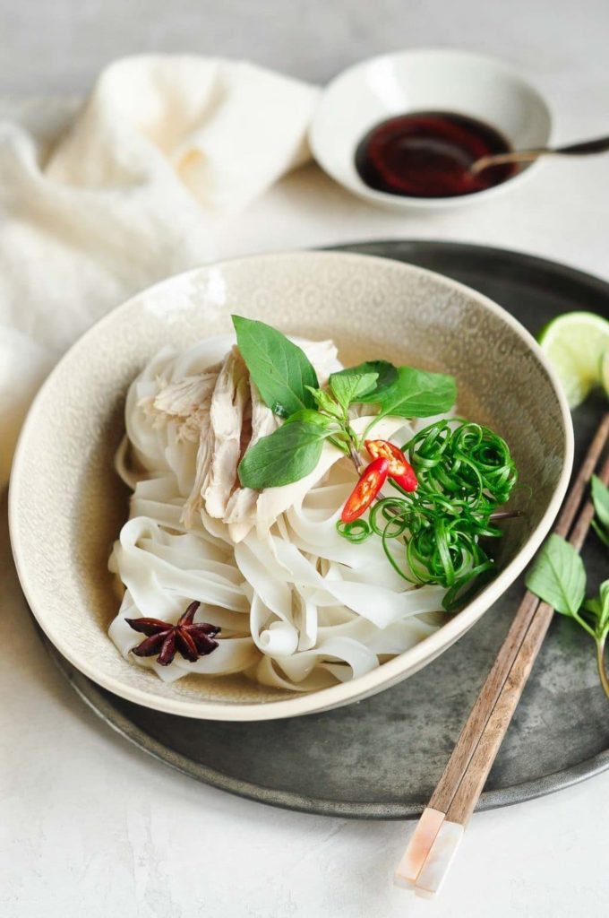 chicken pho recipe with vietnamese chicken pho in bowl on metal tray with wooden chopsticks and white tea towel